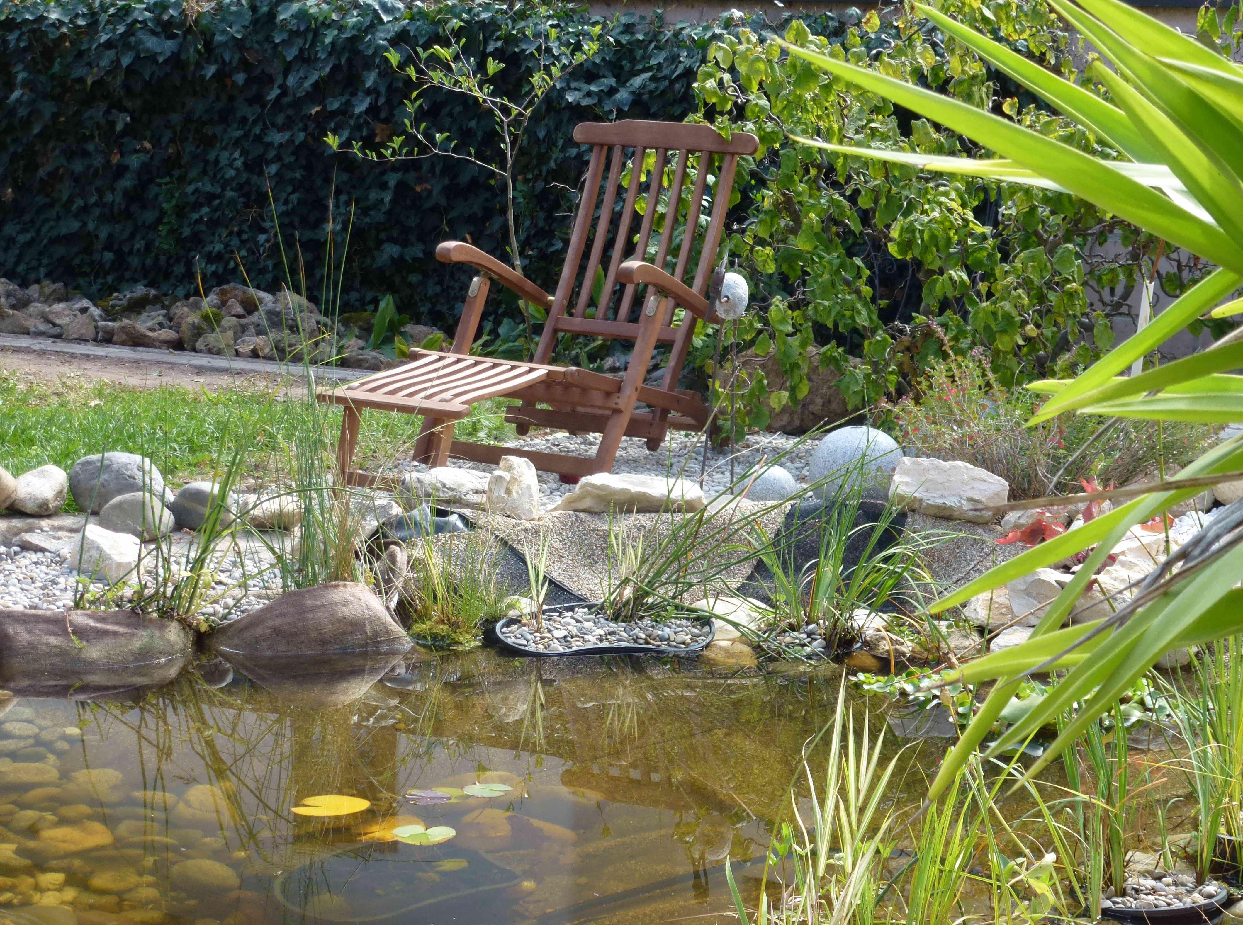 Holzliegestuhl am Teich